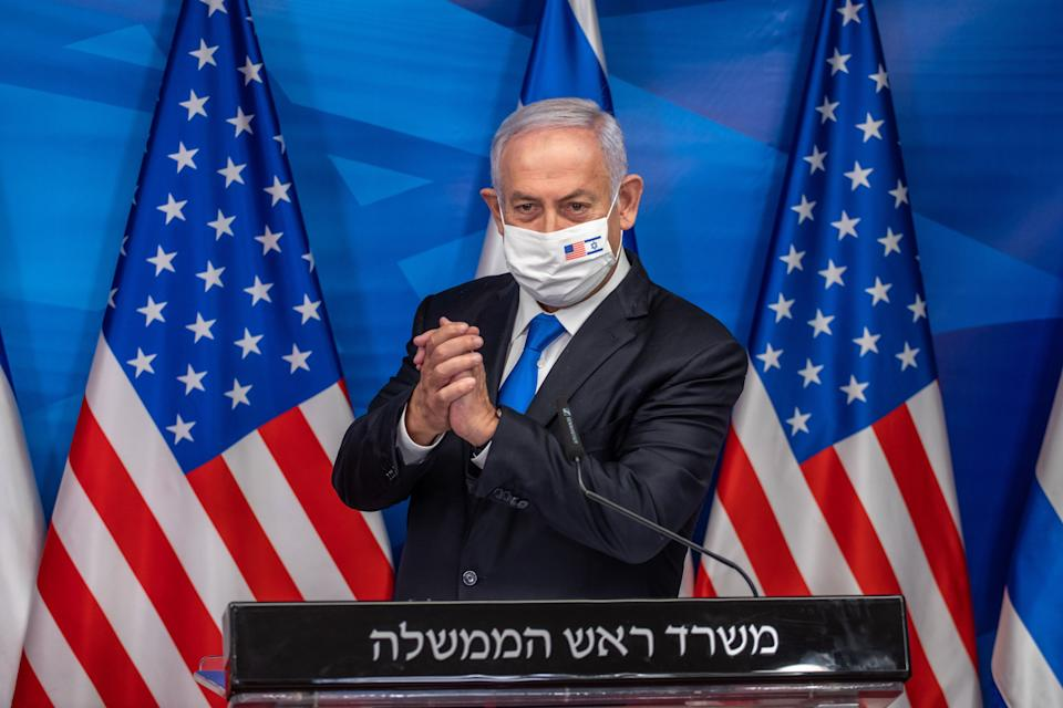 """Israeli Prime Minister Benjamin Netanyahu gives a statement after meeting with the US secretary of treasury in Jerusalem, on January 7, 2021. - Netanyahu condemned as """"disgraceful"""" violence by supporters of his staunch ally President Donald Trump at the US Capitol building. He made the comments in Jerusalem alongside US Treasury Secretary Steven Mnuchin, who called the storming of the Capitol """"unacceptable"""". (Photo by Emil SALMAN / POOL / AFP) (Photo by EMIL SALMAN/POOL/AFP via Getty Images)"""