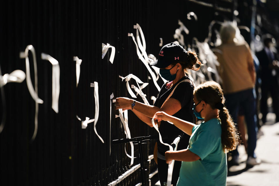 People tie ribbons to the fence at St. Paul's Chapel near the National September 11 Memorial & Museum during a ceremony marking the 20th anniversary of the 9/11 terrorist attacks, Saturday, Sept. 11, 2021, in New York. (AP Photo/Matt Rourke)