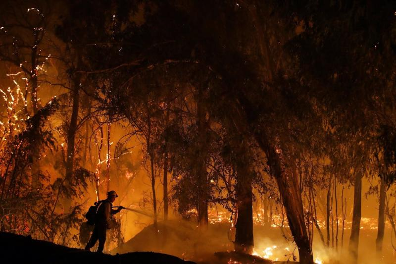 Silhouette of a firefighter in a forest aflame.