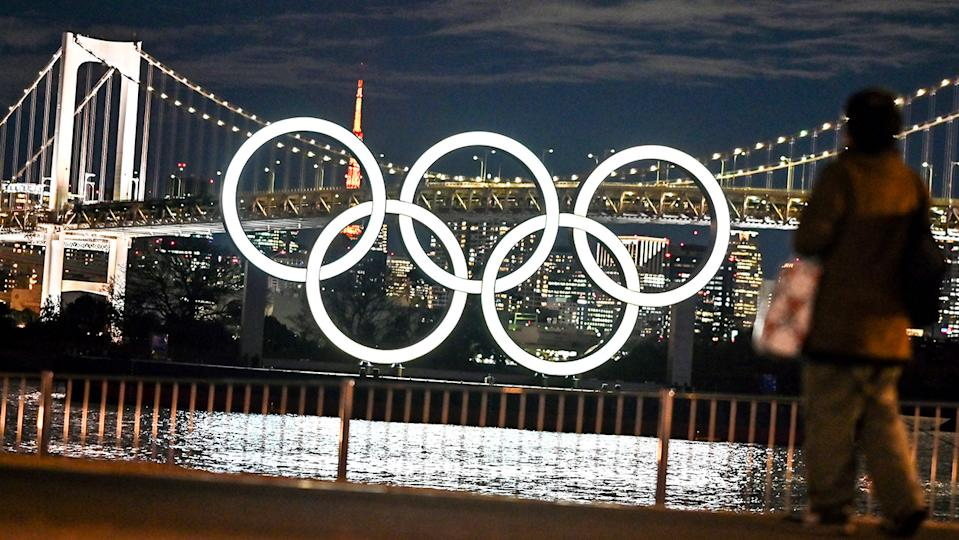 Residents walk past the Olympic rings in Tokyo.