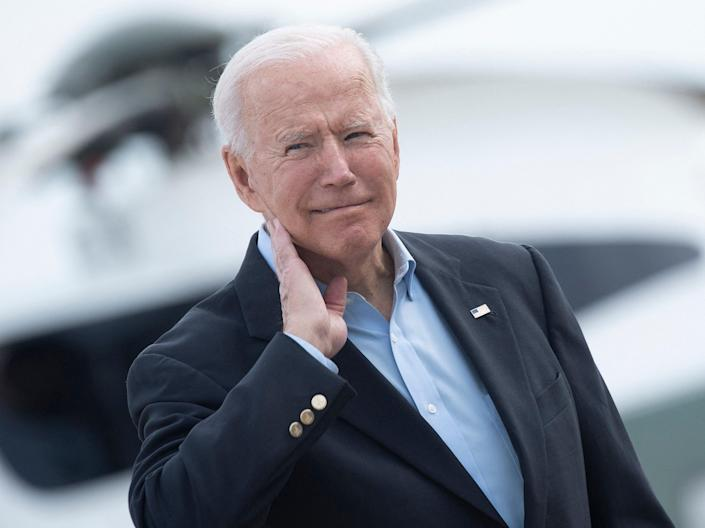 <p>US President Joe Biden wipes his neck after a cicada landed on him while boarding Air Force One at Andrews Air Force Base</p> (AFP via Getty Images)