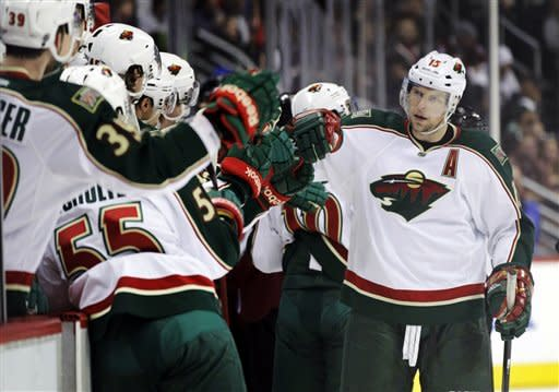 Minnesota Wild players congratulate left wing Dany Heatley, right, after he scored in the first period against the Colorado Avalanche in their NHL hockey game on Tuesday, Jan. 24, 2012, in Denver. (AP Photo/Joe Mahoney)