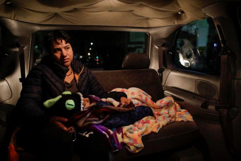Esperanza Paz holds her son, Hermes Soto, as they go to the hospital in Mexico City