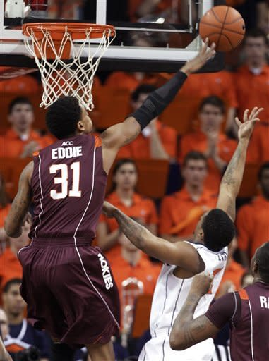 Virginia Tech forward Jarell Eddie (31) blocks a shot by Virginia guard Jontel Evans during the first half of an NCAA college basketball game Tuesday, Feb. 12, 2013, in Charlottesville, Va. (AP Photo/Steve Helber)