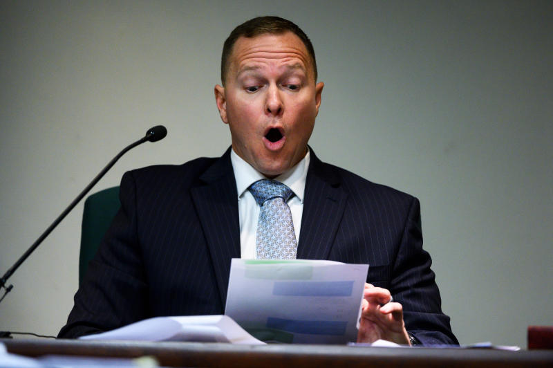 Suspended Greenville Sheriff Will Lewis reads text messages in court, Thursday afternoon, Oct. 24, 2019, in Greenville, S.C. Lewis, 43, said he did not plan to have sex with his young female assistant at an out-of-town budget conference, but one thing led to another after they went out for drinks and ended up in her hotel room.(Josh Morgan/The Greenville News via AP, Pool)
