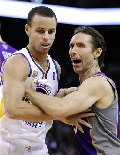 Golden State Warriors' Stephen Curry, left, guards against Phoenix Suns' Steve Nash during the first half of an NBA basketball game, Monday, Feb. 13, 2012, in Oakland, Calif. (AP Photo/Ben Margot)