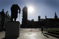 The statue of Winston Churchill is silhouetted in front of Britain's Houses of Parliament as the country is in lockdown to help curb the spread of coronavirus, in London, Tuesday, April 21, 2020. Britain's Parliament is going back to work, and the political authorities have a message for lawmakers: Stay away. U.K. legislators and most parliamentary staff were sent home in late March as part of a nationwide lockdown to slow the spread of the new coronavirus. With more than 16,500 people dead and criticism growing of the government's response to the pandemic, legislators are returning Tuesday — at least virtually — to grapple with the crisis. (AP Photo/Kirsty Wigglesworth)