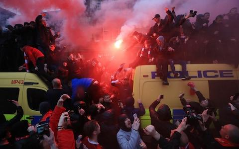 Liverpool fans fashion perches atop Merseyside police vans - Credit: Peter Byrne/PA