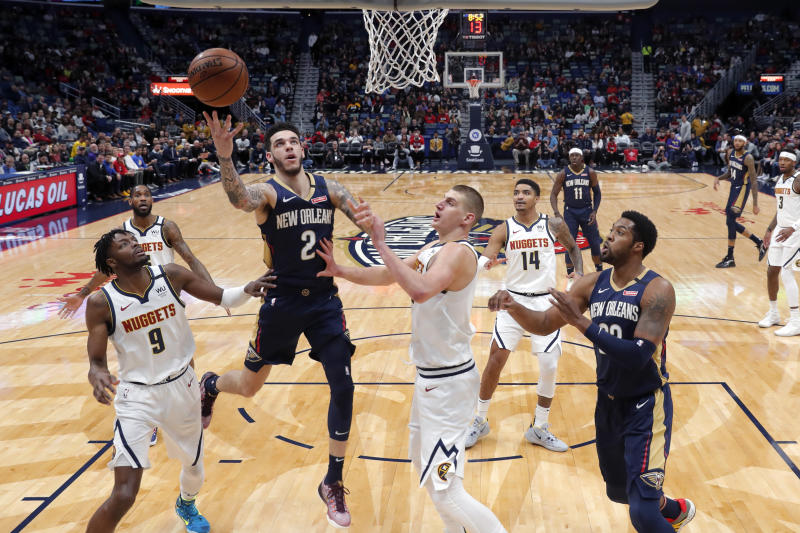 New Orleans Pelicans guard Lonzo Ball (2) goes to the basket between Denver Nuggets forward Jerami Grant (9) and center Nikola Jokic in the first half of an NBA basketball game in New Orleans, Friday, Jan. 24, 2020. (AP Photo/Gerald Herbert)