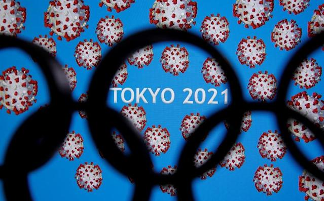 "A 3D printed Olympics logo is seen in front of displayed ""Tokyo 2021"" words in this illustration"