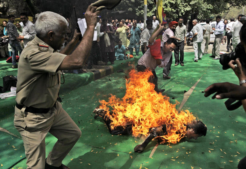An Indian police officer and a protester try to extinguish the fire as a Tibetan man is engulfed in flames after self-immolating at a protest in New Delhi, India, ahead of Chinese President Hu Jintao's visit to the country Monday, March 26, 2012. The Tibetan activist lit himself on fire at the gathering and was rushed to hospital with unknown injuries, reports said. (AP Photo/Manish Swarup)