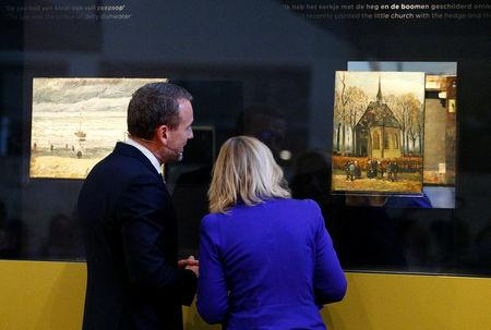 Museum director Axel Ruger and Dutch Minister of Education, Culture and Science Jet Bussemaker reveal two recovered paintings by Vincent van Gogh, which were stolen from the museum in 2002, at the van Gogh Museum in Amsterdam
