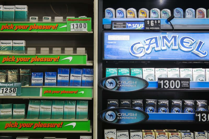 Newport and Camel cigarettes are stacked on a shelf inside a tobacco store in New York
