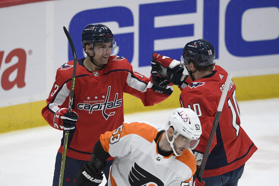 Washington Capitals left wing Conor Sheary (73) celebrates his goal with right wing Daniel Sprong (10) during the first period of an NHL hockey game, next to Philadelphia Flyers defenseman Shayne Gostisbehere (53), Tuesday, April 13, 2021, in Washington. (AP Photo/Nick Wass)