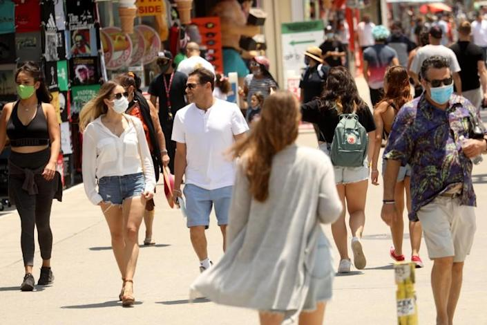 """VENICE, CA - JULY 05, 2020 - - People, some with a mask, others without, walk along the Venice Boardwalk in Venice on July 5, 2020. In what officials have described as an """"alarming"""" increase, hospitalizations of patients with confirmed coronavirus infections in Los Angeles County have jumped 41% in the last three weeks. On Friday, there were 1,947 patients in L.A. County hospitals with confirmed coronavirus infections; seven days earlier, there were 1,717; the week before that, there were 1,426; and the week prior to that, there were 1,383. (Genaro Molina / Los Angeles Times)"""