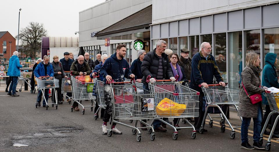 People queue to shop at Sainsbury's supermarket in Leamington Spa, Warwickshire, where the store had announced that the first hour of opening would be for elderly and vulnerable customers.