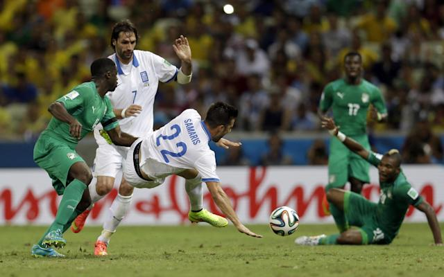 Greece's Andreas Samaris, center, is tackled by Ivory Coast's Kolo Toure, left, during the group C World Cup soccer match between Greece and Ivory Coast at the Arena Castelao in Fortaleza, Brazil, Tuesday, June 24, 2014. (AP Photo/Natacha Pisarenko)