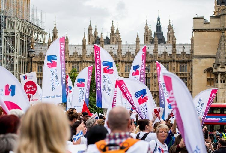 """<span class=""""caption"""">Nurses gather at Parliament Square in London to campaign against the government's 1% public sector pay cap.</span> <span class=""""attribution""""><a class=""""link rapid-noclick-resp"""" href=""""https://www.shutterstock.com/download/confirm/714294907?src=37wX_tPz4Ta_4Eiup6dDPA-1-26&size=medium_jpg"""" rel=""""nofollow noopener"""" target=""""_blank"""" data-ylk=""""slk:John Gomez/Shutterstock.com"""">John Gomez/Shutterstock.com</a></span>"""