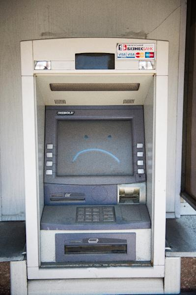 A sad face is edged in dust on the screen of an ATM machine in a closed down bank in central Donetsk, Ukraine, on April 12, 2015 (AFP Photo/Odd Andersen)