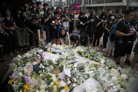 People pay their respects at the site where a man fell from a scaffolding at the Pacific Place complex while protesting against a proposed extradition bill, in Hong Kong