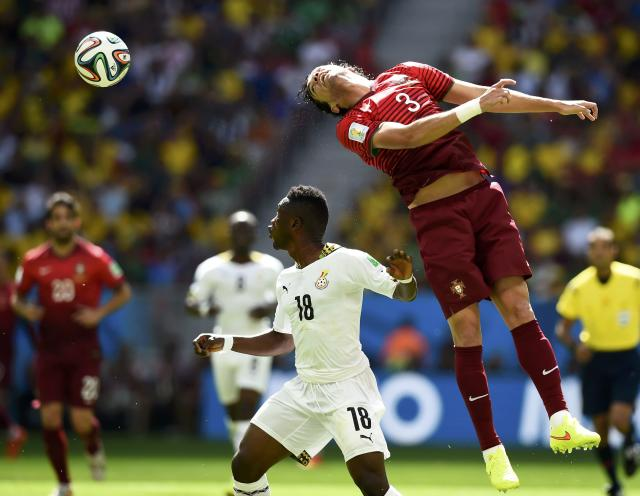 Portugal's Pepe (R) jumps for the ball against Ghana's Abdul Majeed Waris during their 2014 World Cup Group G soccer match at the Brasilia national stadium in Brasilia June 26, 2014. REUTERS/Dylan Martinez (BRAZIL - Tags: SOCCER SPORT WORLD CUP TPX IMAGES OF THE DAY)