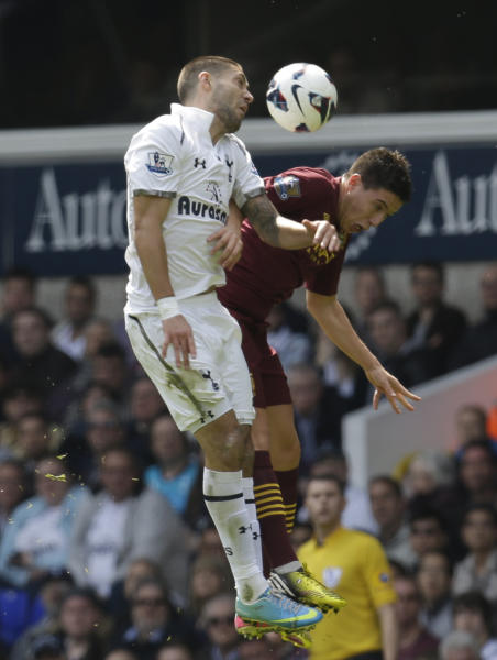 CORRECTING SPELLING OF NAME DEMPSEY - Tottenham Hotspur's Clint Dempsey, left, fights for the ball with Manchester City's Samir Nasri, during their English Premier League soccer match at White Hart Lane in London, Sunday, April 21, 2013. Tottenham Hotspur won the match 3-1. (AP Photo/Lefteris Pitarakis)