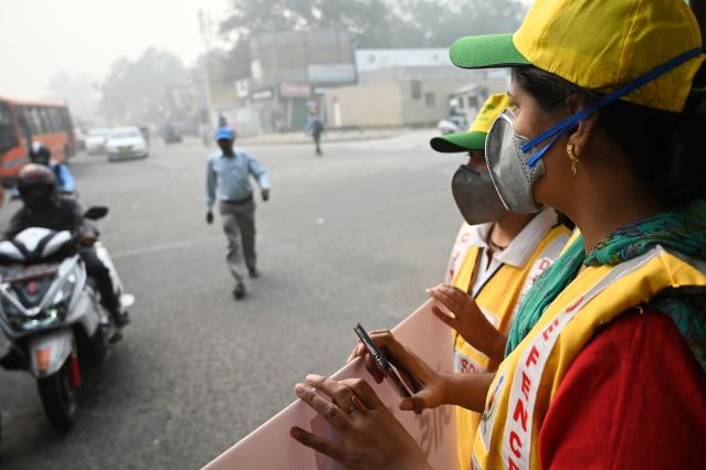 Volunteers from civil defence display a placard to aware drivers on a street after the local government ordered half of the city's private cars to be taken off the road based on an odd-even registration plate system to help reduce air pollution, in New Delhi on Nov. 4, 2019. (Photo: Money Sharma/AFP via Getty Images)