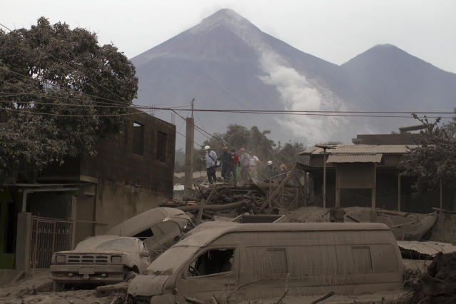 "<p>Rescue workers walk on rooftops in Escuintla, Guatemala, June 4, 2018, blanketed with heavy ash spewed by the Volcan de Fuego, or ""Volcano of Fire,"" pictured in the background, left center. (Photo: Luis Soto/AP) </p>"
