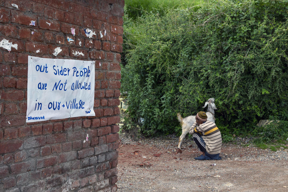 An elderly man sits with his goat at the entrance of Naddi village with a signboard denying entrance to outsiders stuck on a wall in Dharmsala, India, Saturday, June 12, 2021. (AP Photo/Ashwini Bhatia)