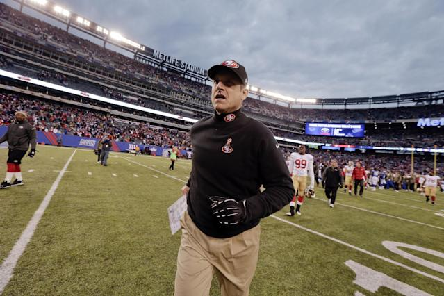 FILE - In this Nov. 16, 2014, file photo, San Francisco 49ers head coach Jim Harbaugh leaves the field after an NFL football game against the New York Giants in East Rutherford, N.J. Harbaugh was in discussions with Michigan to return to his alma mater as its new football coach, a person with knowledge of the talks said Monday, Dec. 29. The person spoke to The Associated Press on condition of anonymity because there was no announcement from the school or Harbaugh, who left the NFL team Sunday following its season finale. (AP Photo/Julio Cortez, File)