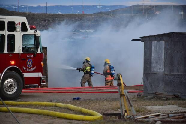 Firefighters in Iqaluit work to extinguish a fire. In 2020, Nunavut experienced 131 fires, which resulted in two deaths, six injuries and $5.7 million in damages, according to the territorial fire marshal's annual report. (Patrick Nagle/CBC  - image credit)