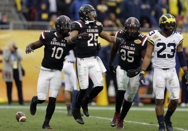 South Carolina's A.J. Turner (25) celebrates with Skai Moore (10) and Daniel Fennell (35) after recovering a fumble by Michigan during the second half of the Outback Bowl NCAA college football game Monday, Jan. 1, 2018, in Tampa, Fla. South Carolina won the game 26-19. (AP Photo/Chris O'Meara)