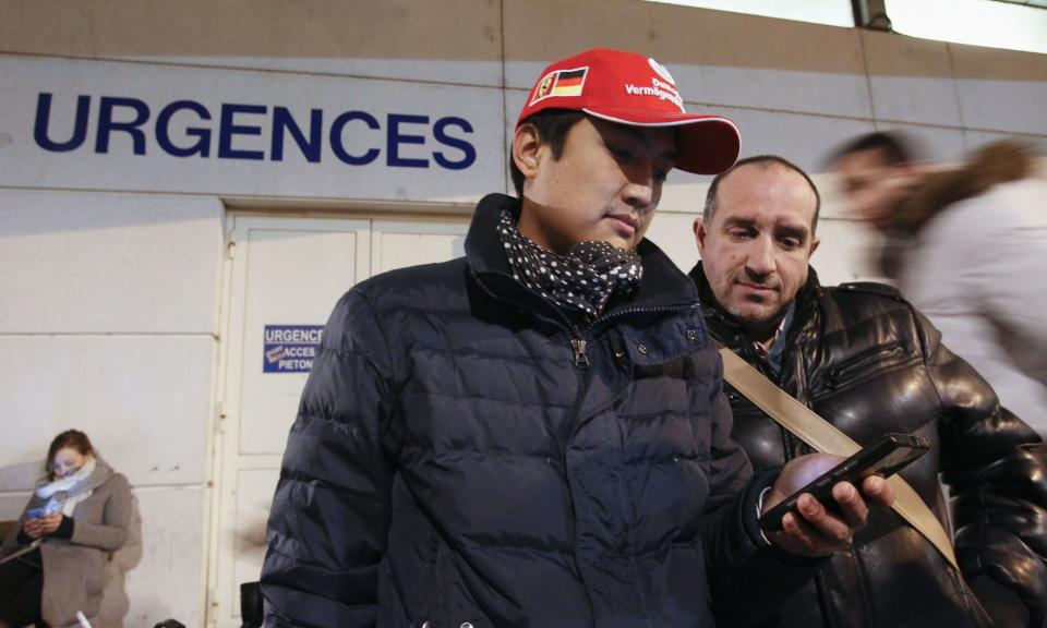 A fan wearing a red cap with a German flag on it stands outside the CHU Nord hospital emergency unit in Grenoble, French Alps, where retired seven-times Formula One world champion Michael Schumacher is reported to be hospitalized after a ski accident, December 29, 2013. Schumacher suffered a head injury in a fall while skiing off-piste in the French Alps resort of Meribel on Sunday, an official said. The 44-year-old German was wearing a helmet and was conscious while being transported to a local hospital before later being transferred to to a better-equipped medical unit in Grenoble for further examinations. (REUTERS/Robert Pratta)