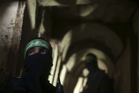 Palestinian fighters from the Izz el-Deen al-Qassam Brigades, the armed wing of the Hamas movement, stand inside an underground tunnel in Gaza
