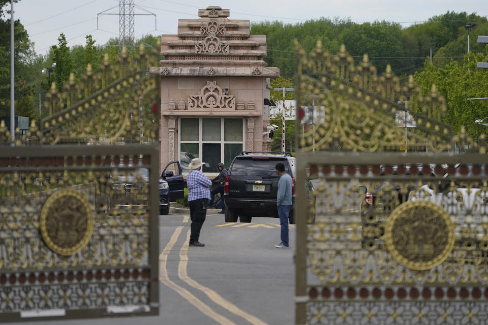 People stand near the entrance to the BAPS Shri Swaminarayan Mandir in Robbinsville Township, N.J., Tuesday, May 11, 2021. Workers from marginalized communities in India were lured to the U.S. and forced to work long hours for just a few dollars per day to help build the Hindu temple in New Jersey, according to a lawsuit filed Tuesday, May 11, 2021. The lawsuit filed in federal court accuses the leaders of the Hindu organization known as Bochasanwasi Akshar Purushottam Swaminarayan Sanstha, or BAPS, of human trafficking and wage law violations. (AP Photo/Seth Wenig)