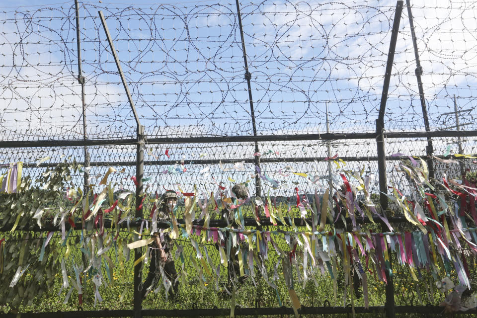 """South Korean army soldiers wearing face masks to help protect against the spread of the new coronavirus pass by a wire fence decorated with ribbons written with messages wishing for the reunification of the two Koreas at the Imjingak Pavilion in Paju, near the border with North Korea, Sunday, July 26, 2020. North Korean leader Kim Jong Un placed the city of Kaesong near the border with South Korea under total lockdown after a person was found with suspected COVID-19 symptoms, saying he believes """"the vicious virus"""" may have entered the country, state media reported Sunday. (AP Photo/Ahn Young-joon)"""