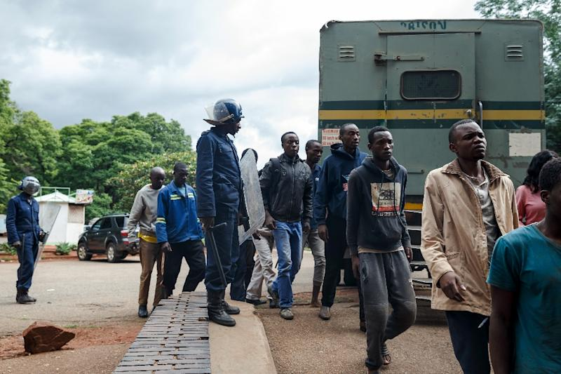 Zimbabwean anti-riot police forces watch men arrested during violent protests triggered by a sudden rise in fuel prices announced by Zimbabwean president, before their hearing at the Law Court in Harare on January 16, 2019