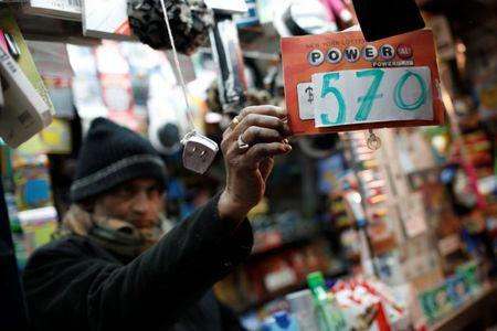 A vendor who sells lottery tickets hangs a sign for the Powerball drawing at a news stand in midtown Manhattan in New York City, New York, U.S., January 5, 2018. REUTERS/Mike Segar