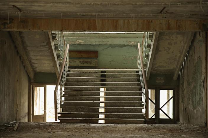 <p>A stairwell stands in abandoned elementary school (Getty Images) </p>
