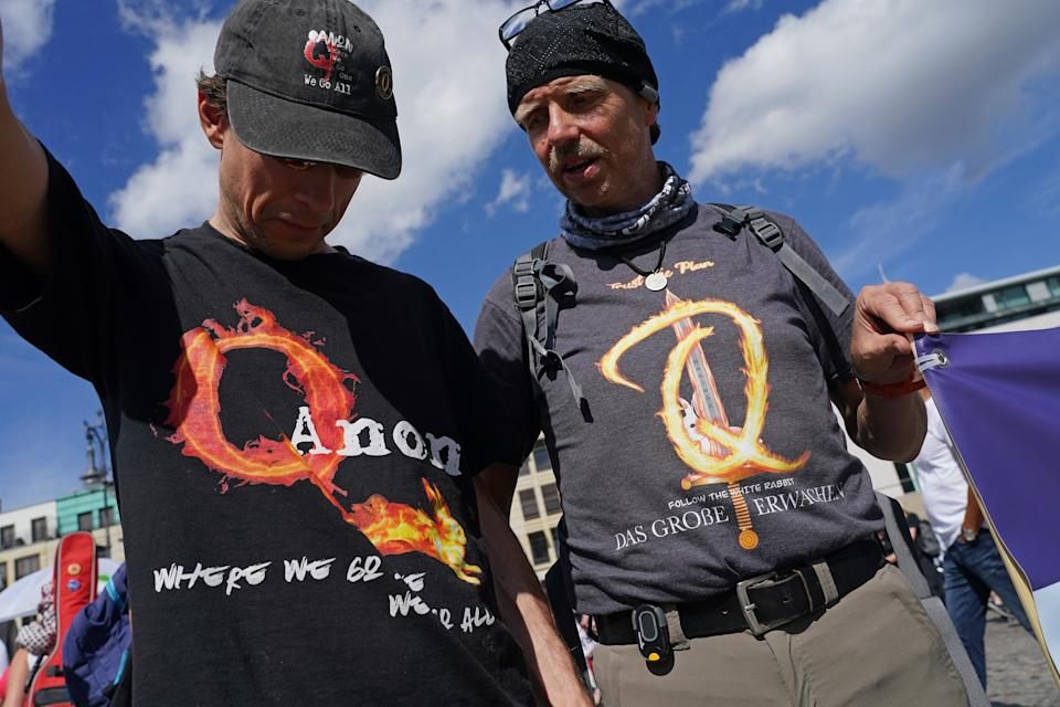 BERLIN, GERMANY - AUGUST 29: QAnon conspiracy supporters attend a protest of coronavirus skeptics, right-wing extremists and others angry over coronavirus-related restrictions and government policy on August 29, 2020 in Berlin, Germany. City authorities had banned the planned protest, citing the flouting of social distancing by participants in a similar march that drew at least 17,000 people a few weeks ago, but a court overturned the ban. (Photo by Sean Gallup/Getty Images)