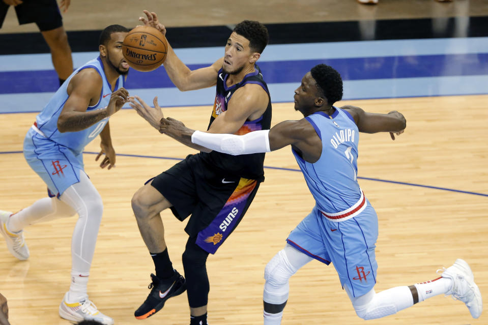 Phoenix Suns guard Devin Booker, middle, loses the ball on a shot attempt as he is fouled by Houston Rockets guard Victor Oladipo (7), while guard Sterling Brown, left, watches during the second half of an NBA basketball game Wednesday, Jan. 20, 2021, in Houston. (AP Photo/Michael Wyke)