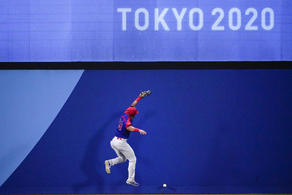 Dominican Republic's Jose Bautista cannot reach a ball hit by South Korea's Kyoungmin Hur in the second inning of a baseball game at the 2020 Summer Olympics, Sunday, Aug. 1, 2021, in Yokohama, Japan. (AP Photo/Sue Ogrocki)