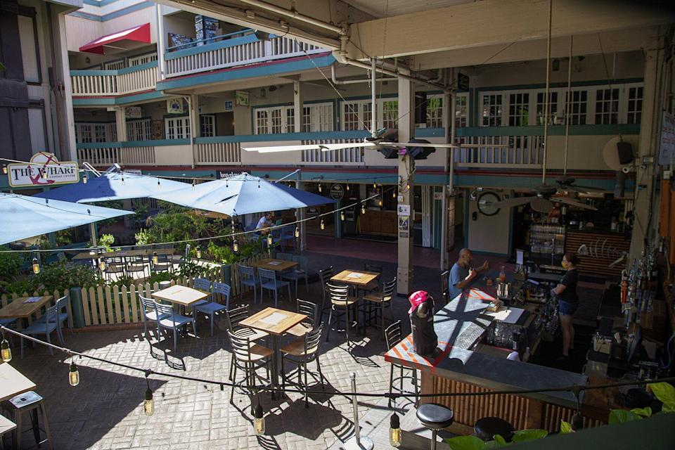 Outside seating is seen empty at a restaurant at The Wharf in Lahaina, Maui County, Hawaii