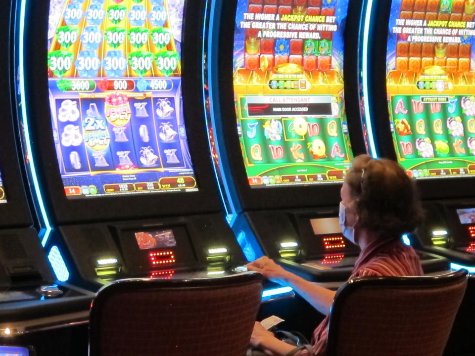 In this July 2, 2020 photo, a woman plays a slot machine at the Golden Nugget casino in Atlantic City N.J. Gambling companies in the U.S. are increasingly bringing different forms of gambling together, including sports betting, casino gambling, internet gambling and daily fantasy sports, and partnering with media companies as they seek to increase revenue. (AP Photo/Wayne Parry)
