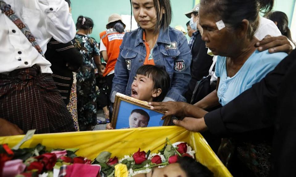 The daughter of Zwee Htet-soe, who died in the anti-coup protests, cries near the coffin of her father during his funeral in Yangon, Myanmar.