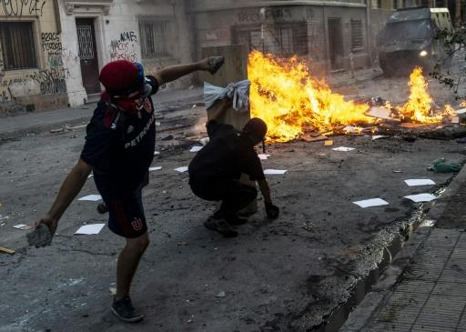 Demonstrators clash with the police during Monday night's anti-government protests in the Chilean capital Santiago