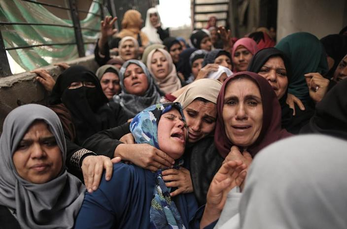 Palestinian relatives of Hamdan Abu Amsha, killed a day earlier by Israeli forces, cry during his funeral in Beit Hanun in the north of the Gaza Strip on March 31, 2018 (AFP Photo/MAHMUD HAMS)