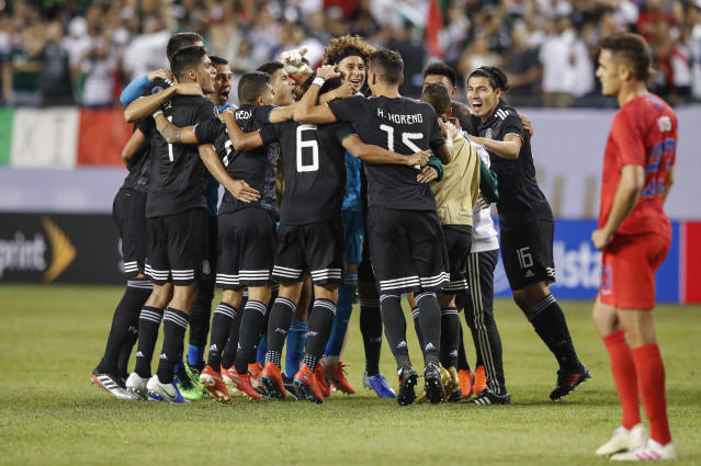 """U.S. defender <a class=""""link rapid-noclick-resp"""" href=""""/soccer/players/414969/"""" data-ylk=""""slk:Aaron Long"""">Aaron Long</a> looks away as Mexico celebrates its 2019 Gold Cup title. (Getty)"""