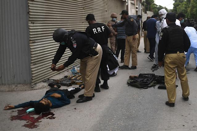 EDITORS NOTE: Graphic content / Police collect evidence next to a body of an alleged gunman outside the Pakistan Stock Exchange building in Karachi on June 29, 2020. - A group of gunmen attacked the Pakistan Stock Exchange in Karachi June 29, police said, with four of the attackers killed. (Photo by Asif HASSAN / AFP) (Photo by ASIF HASSAN/AFP via Getty Images)