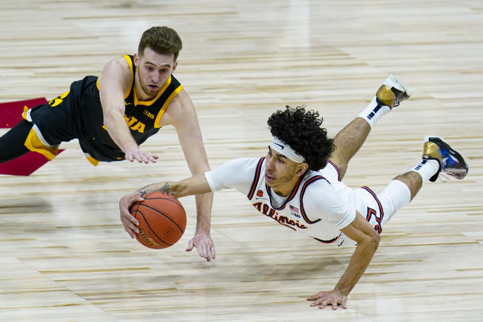 Illinois guard Andre Curbelo (5) dives to make a steal under Iowa guard Jordan Bohannon (3) in the second half of an NCAA college basketball game at the Big Ten Conference tournament in Indianapolis, Saturday, March 13, 2021. (AP Photo/Michael Conroy)